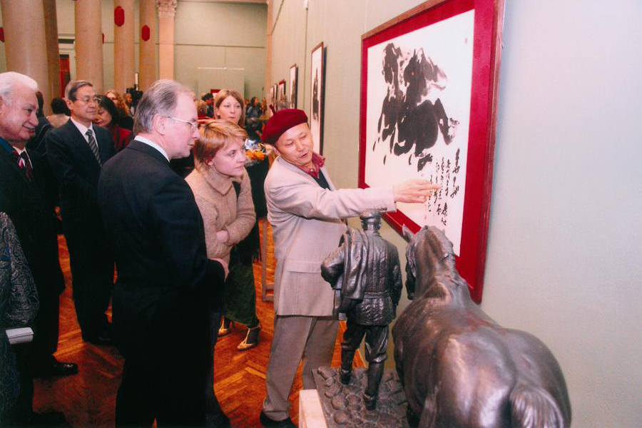 """在白俄罗斯举办的""""神马画展""""上,阎飞鸿介绍展会作品之一《奔驰》"""